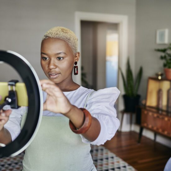 Young African female influencer adjusting a smart phone and ring light before doing an online vlog post at home